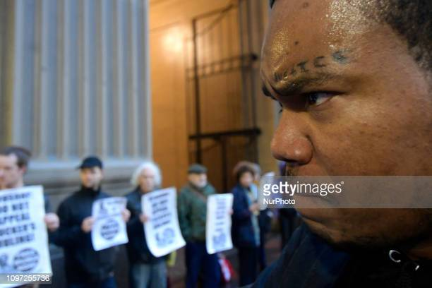 Justice reads a tattoo on the face of activist Diop Olugbala of North Philadelphia at a rally outside the District Attorneys Office in Philadelphia...