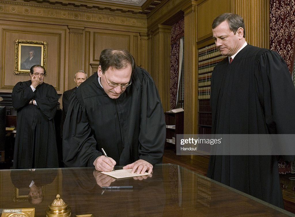 Justice Samuel A. Alito, Jr. (2nd R) signs his oath card in the Justices' Conference Room as Chief Justice John G. Roberts, Jr. looks on with Justices Anitonin Scalia and David Souter in the background, February 16, 2006 at the Supreme Court in Washington, DC.
