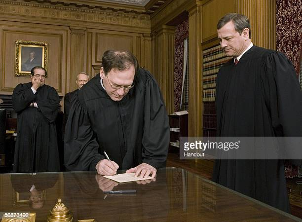 Justice Samuel A Alito Jr signs his oath card in the Justices' Conference Room as Chief Justice John G Roberts Jr looks on with Justices Anitonin...