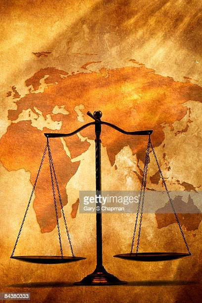 Justice scale in front of western hemisphere map.