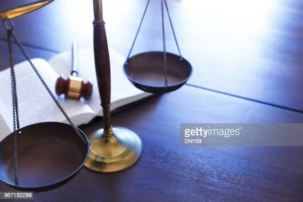 justice scale sitting in front of an open law book - equal arm balance stock pictures, royalty-free photos & images