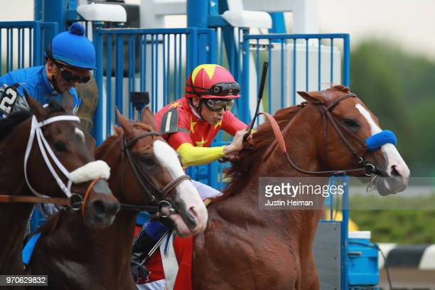 Justify ridden by jockey Mike Smith breaks from the gate during the 150th running of the Belmont Stakes at Belmont Park on June 9 2018 in Elmont New...