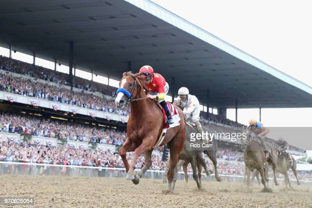 Justify ridden by jockey Mike Smith crosses the finish line to win the 150th running of the Belmont Stakes at Belmont Park on June 9 2018 in Elmont...