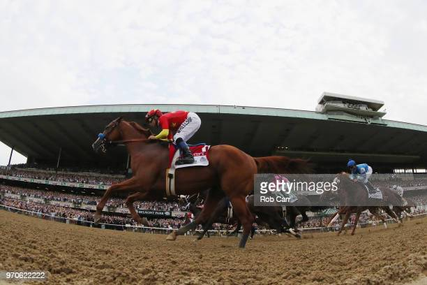 Justify ridden by jockey Mike Smith heads into the first turn during the 150th running of the Belmont Stakes at Belmont Park on June 9 2018 in Elmont...