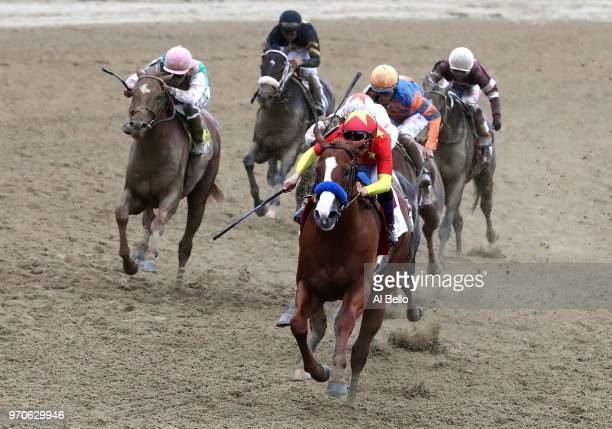 Justify ridden by jockey Mike Smith leads the field during the 150th running of the Belmont Stakes at Belmont Park on June 9 2018 in Elmont New York...