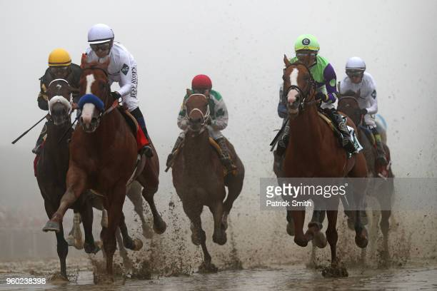 Justify ridden by jockey Mike Smith leads the field in the first pass the 143rd running of the Preakness Stakes at Pimlico Race Course on May 19 2018...