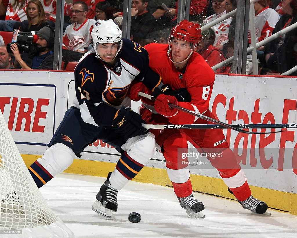 Justin Abdelkader #8 of the Detroit Red Wings and Jim Slater #23 of the Atlanta Thrashers battle for the puck behind the net during a NHL game at Joe Louis Arena on November 25, 2009 in Detroit, Michigan.
