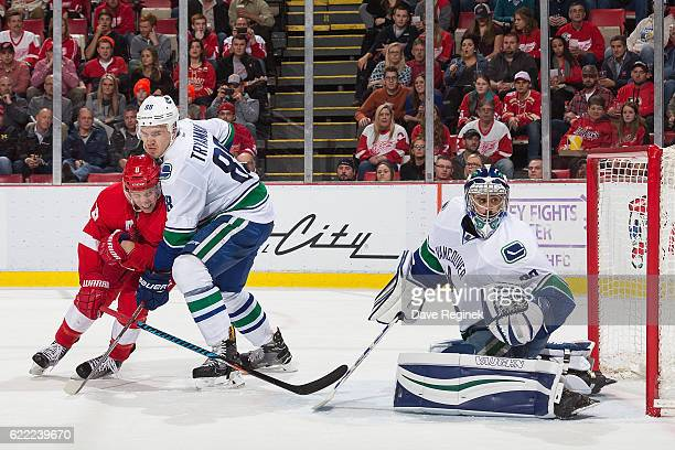 Justin Abdelkader of the Detroit Red Wings battles in front of the net with Nikita Tryamkin of the Vancouver Canucks as goaltender Ryan Miller of the...