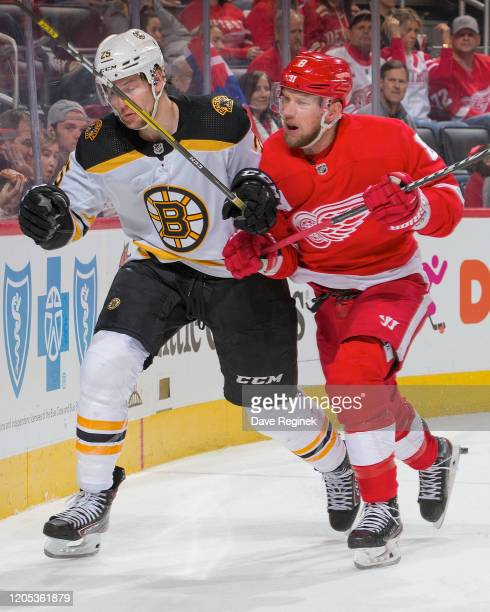 Justin Abdelkader of the Detroit Red Wings body checks Brandon Carlo of the Boston Bruins during an NHL game at Little Caesars Arena on February 9,...