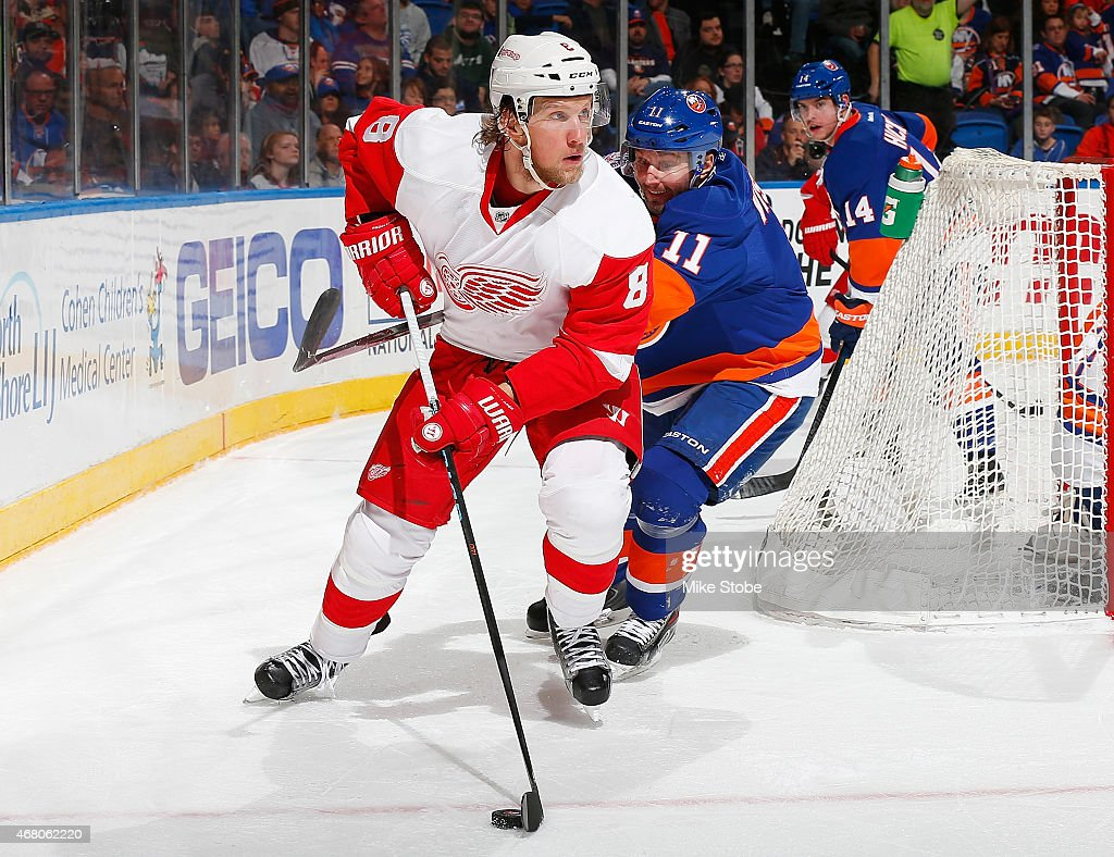 Justin Abdelkader #8 of the Detroit Red Wings controls the puck in front of Lubomir Visnovsky #11 of the New York Islanders at Nassau Veterans Memorial Coliseum on March 29, 2015 in Uniondale, New York. The Islanders defeated the Red Wings 5-4.