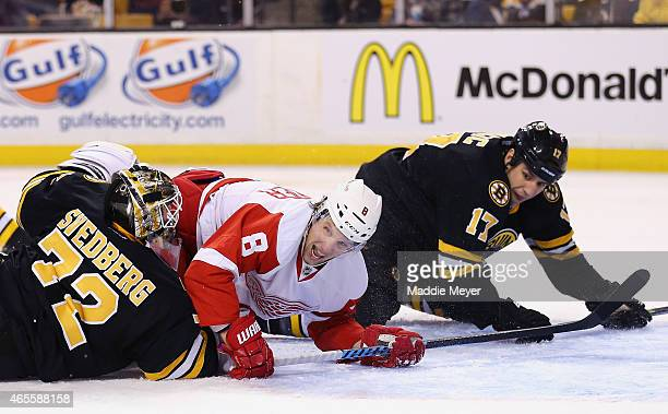 Justin Abdelkader of the Detroit Red Wings falls over Niklas Svedberg in an attempt to score defended by Milan Lucic of the Boston Bruins in the...