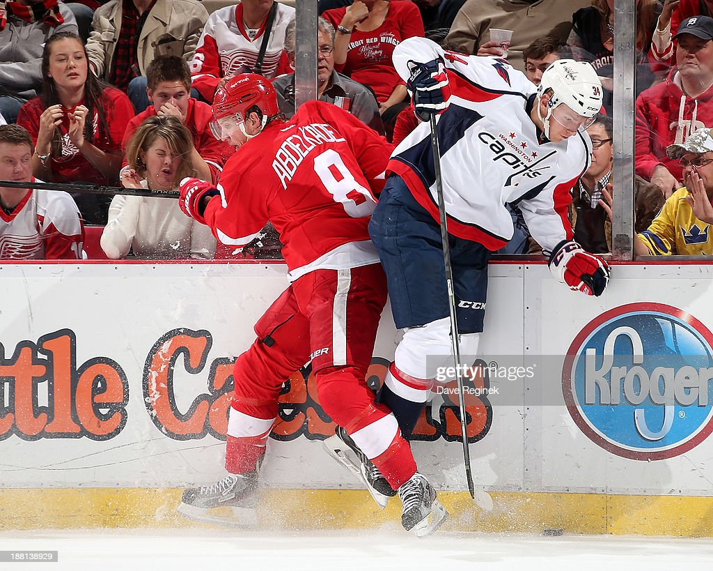 Justin Abdelkader #8 of the Detroit Red Wings hits Alexander Urbom #34 of the Washington Capitals during an NHL game at Joe Louis Arena on November 15, 2013 in Detroit, Michigan. The Capitals defeated the Wings 4-3 in a shootout.