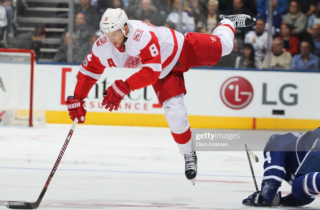 Justin Abdelkader #8 of the Detroit Red Wings is sent flying by Morgan Rielly #44 of the Toronto Maple Leafs in an NHL game at the Air Canada Centre on October 18, 2017 in Toronto, Ontario. The Maple Leafs defeated the Red Wings 6-3.