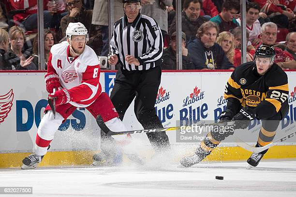 Justin Abdelkader of the Detroit Red Wings races for the puck with Brandon Carlo of the Boston Bruins during an NHL game at Joe Louis Arena on...