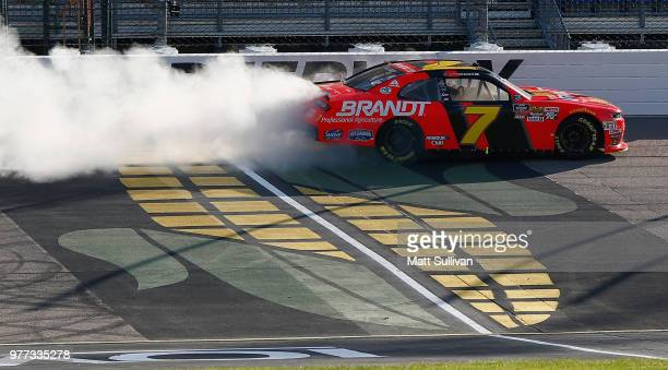Justin Allgaier driver of the BRANDT Professional Agriculture Chevrolet celebrates by doing a burn out after winning the NASCAR Xfinity Series Iowa...