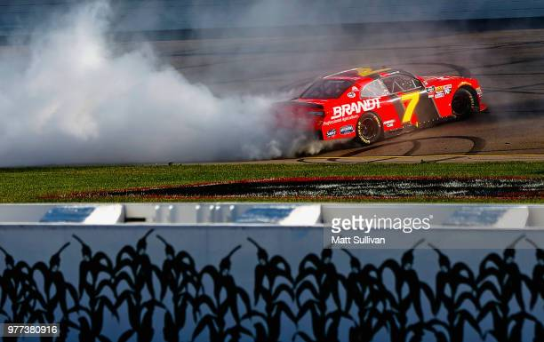Justin Allgaier driver of the BRANDT Professional Agriculture Chevrolet celebrates by doing a burnout after winning the NASCAR Xfinity Series Iowa...