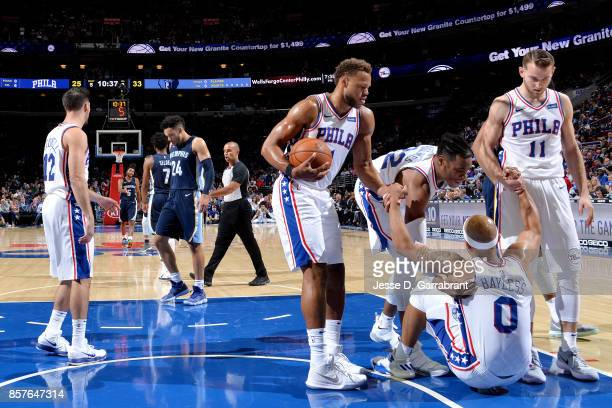 Justin Anderson Richaun Holmes and Nik Stauskas help up Jerryd Bayless of the Philadelphia 76ers during the game against the Memphis Grizzlies during...