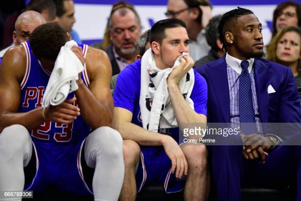 Justin Anderson TJ McConnell and Robert Covington of the Philadelphia 76ers look on from the bench against the Milwaukee Bucks during the fourth...