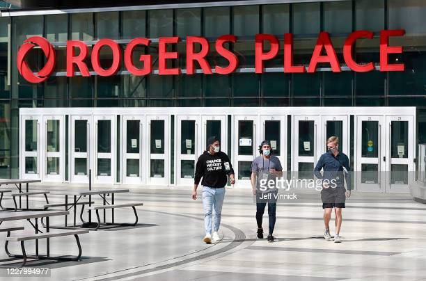 Justin Bailey, Jalen Chatfield and Olli Juolevi of the Vancouver Canucks wear protective face masks as they leave Rogers Place after coronavirus...