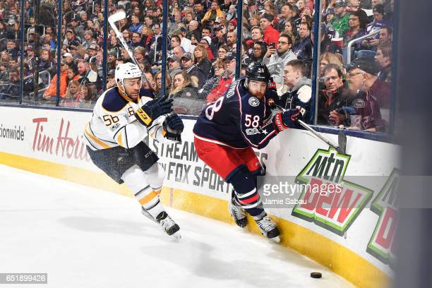 Justin Bailey of the Buffalo Sabres and David Savard of the Columbus Blue Jackets skate after a loose puck during the second period of a game on...