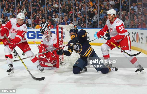 Justin Bailey of the Buffalo Sabres battles Dylan Larkin and Mike Green of the Detroit Red Wings in the offensive zone during an NHL game on October...