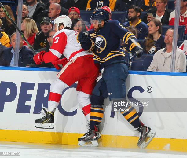 Justin Bailey of the Buffalo Sabres checks Nick Jensen of the Detroit Red Wings during an NHL game on October 24, 2017 at KeyBank Center in Buffalo,...