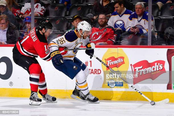 Justin Bailey of the Buffalo Sabres is pursued by PA Parenteau of the New Jersey Devils during the third period at Prudential Center on February 6...