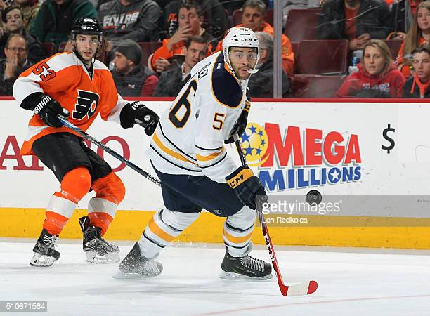 Justin Bailey of the Buffalo Sabres making his NHL debut skates after the air bourn puck against Shayne Gostisbehere of the Philadelphia Flyers on...