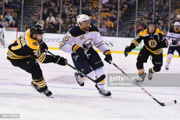 Justin Bailey of the Buffalo Sabres reaches for the puck against Patrice Bergeron of the Boston Bruins at the TD Garden on October 21 2017 in Boston...