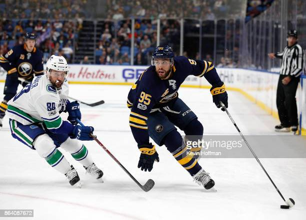 Justin Bailey of the Buffalo Sabres take the puck around Sam Gagner of the Vancouver Canucks during the second period at the KeyBank Center on...