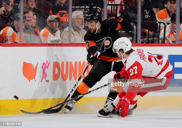 Justin Bailey of the Philadelphia Flyers clears the puck as Michael Rasmussen of the Detroit Red Wings defends at Wells Fargo Center on February 16,...
