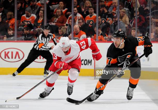Justin Bailey of the Philadelphia Flyers takes the puck as Darren Helm of the Detroit Red Wings defends in the second period at Wells Fargo Center on...