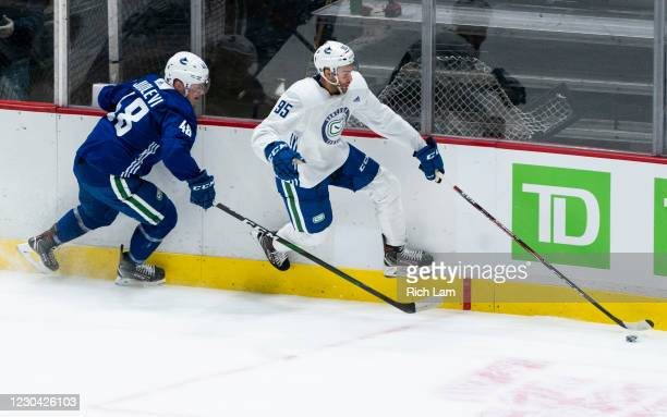 Justin Bailey of the Vancouver Canucks gets past Olli Juolevi along the end boards during a drill on the first day of the Vancouver Canucks NHL...