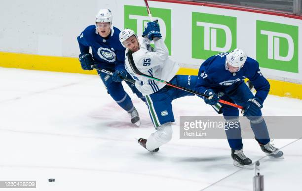Justin Bailey of the Vancouver Canucks gets up ended while trying to get by Tyler Myers and Olli Juolevi during a drill on the first day of the...