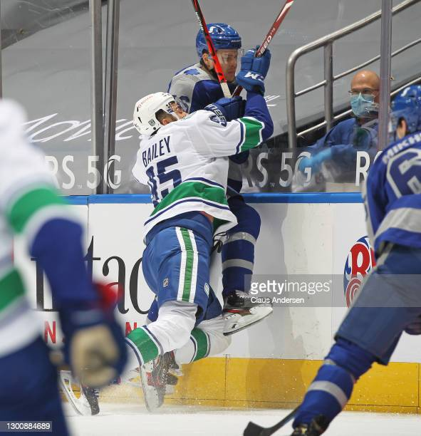 Justin Bailey of the Vancouver Canucks hammers Mikko Lehtonen of the Toronto Maple Leafs into the boards during an NHL game at Scotiabank Arena on...