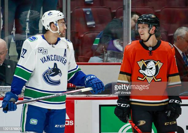 Justin Bailey of the Vancouver Canucks sports a Daniel Sedin jersey as he talks with Brendan Guhle of the Anaheim Ducks during warmup before their...