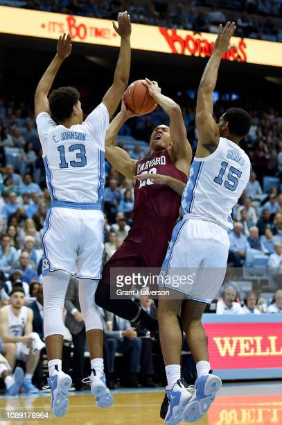 Justin Bassey of the Harvard Crimson drives between Cameron Johnson and Garrison Brooks of the North Carolina Tar Heels during the first half at the...