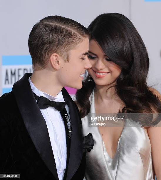 Justin Bieber and Selena Gomez arrive at the 2011 American Music Awards at Nokia Theatre LA Live on November 20 2011 in Los Angeles California