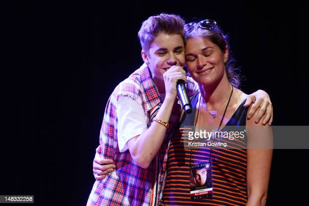 Justin Bieber appears onstage with one of his staff celebrating her birthday during Universal Music Group's press conference at the Trader's Hotel in...