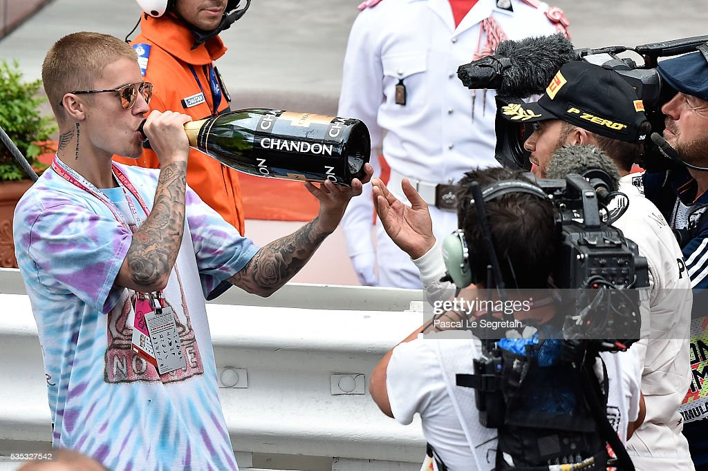 Justin Bieber drinks champagne from the bottle of F1 Grand Prix of Monaco winner, Lewis Hamilton of Great Britain during the podium ceremony on May 29, 2016 in Monte-Carlo, Monaco.