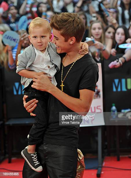 Justin Bieber holding his brother Jaxon poses for a photos on the red carpet at the 2012 MMVAs Sunday June 17 2012 VINCE TALOTTA/TORONTO STAR