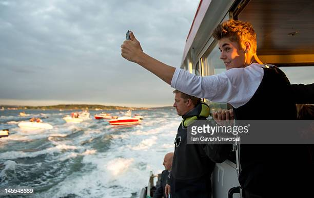 Justin Bieber takes photographs as fans chase after his boat in smaller boats in the harbour after his performance at the Opera House on May 30 2012...