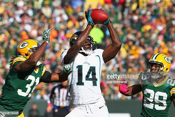 Justin Blackmon of the Jacksonville Jaguars hauls in a pass against Davon House and Casey Hayward of the Green Bay Packers at Lambeau Field on...