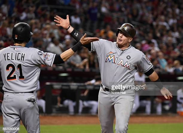 Justin Bour of the Miami Marlins celebrates with teammate Christian Yelich after hitting a three run home run off of Zack Greinke of the Arizona...