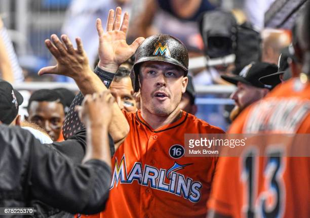 Justin Bour of the Miami Marlins celebrates with teammates in the dugout in the seventh inning during the game between the Miami Marlins and the...
