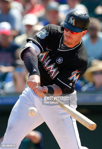 Justin Bour of the Miami Marlins hits a ground ball to shortstop that drives in Ichiro Suzuki in the first inning during a spring training baseball...