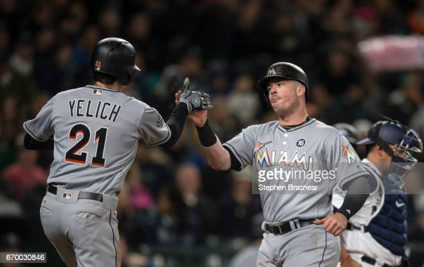 Justin Bour of the Miami Marlins is congratulated by Christian Yelich of the Miami Marlins after Bour hit a tworun home run off of starting pitcher...