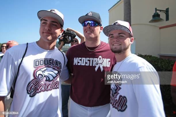 Justin Bour of the Miami Marlins poses with members of the Marjory Stoneman Douglas High School baseball team during a spring training game at Roger...