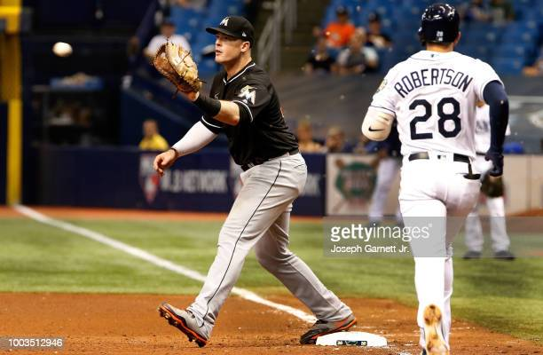 Justin Bour of the Miami Marlins prepares to catch the ball for an out at first base on Daniel Robertson of the Tampa Bay Rays at Tropicana Field on...
