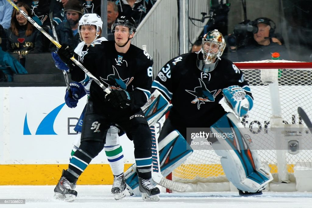 Justin Braun #61 and Aaron Dell #30 of the San Jose Sharks defend against Markus Granlund #60 of the Vancouver Canucks at SAP Center at San Jose on March 2, 2017 in San Jose, California.